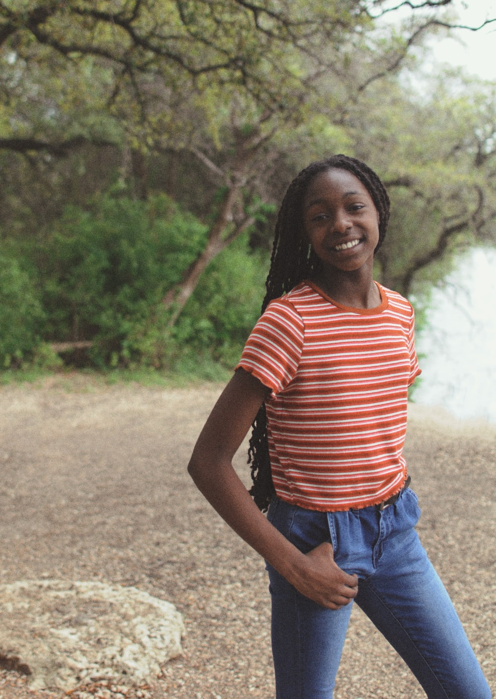 woman in red and white striped shirt and blue denim jeans standing on dirt road during