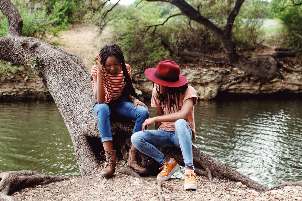 woman in red hat and blue denim jeans sitting on tree trunk beside river during daytime