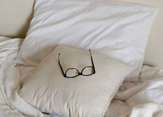 black framed eyeglasses on white throw pillow
