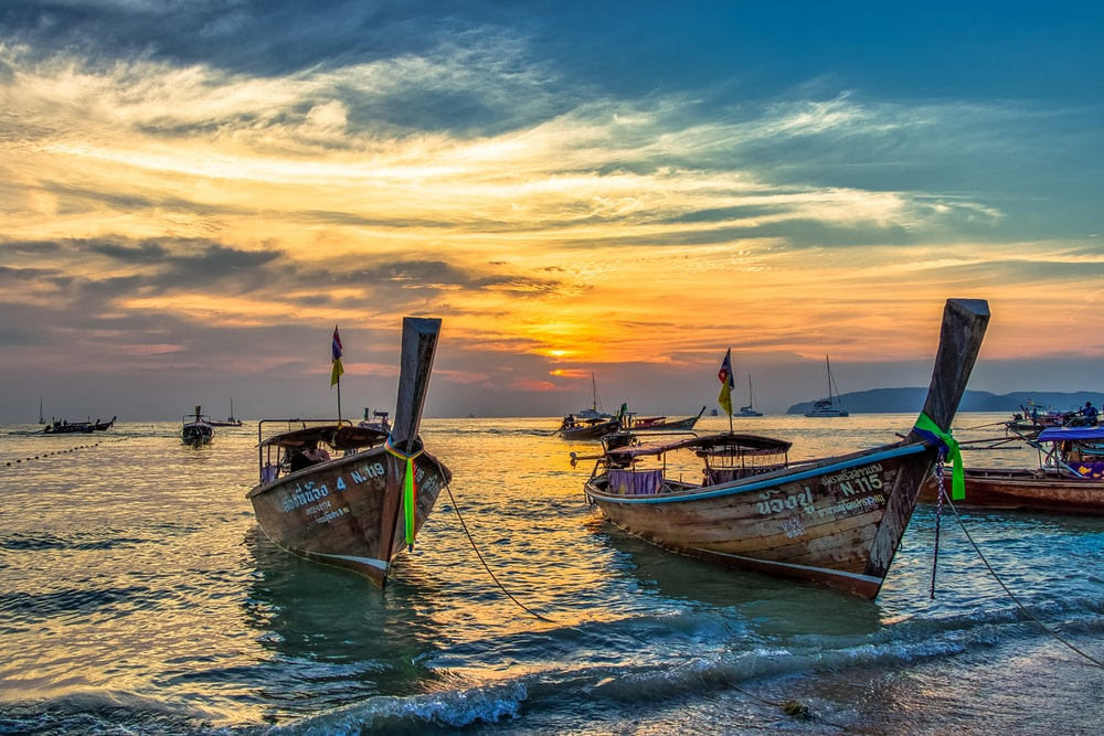white and blue boat on sea during sunset