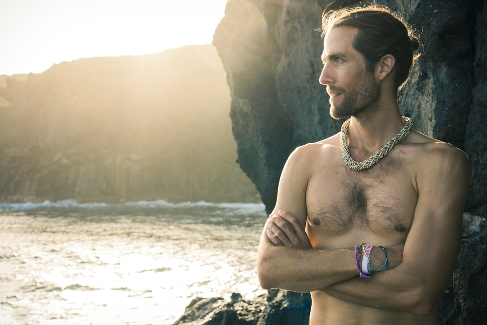 topless man wearing silver necklace standing on beach during daytime