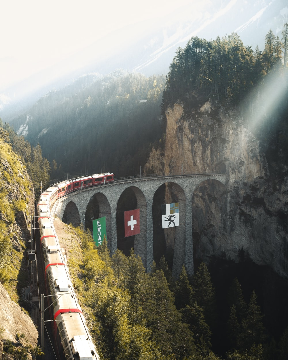 red train on rail near mountain during daytime