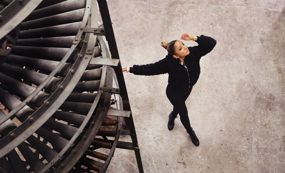 woman in black jacket and black pants walking on brown wooden stairs during daytime