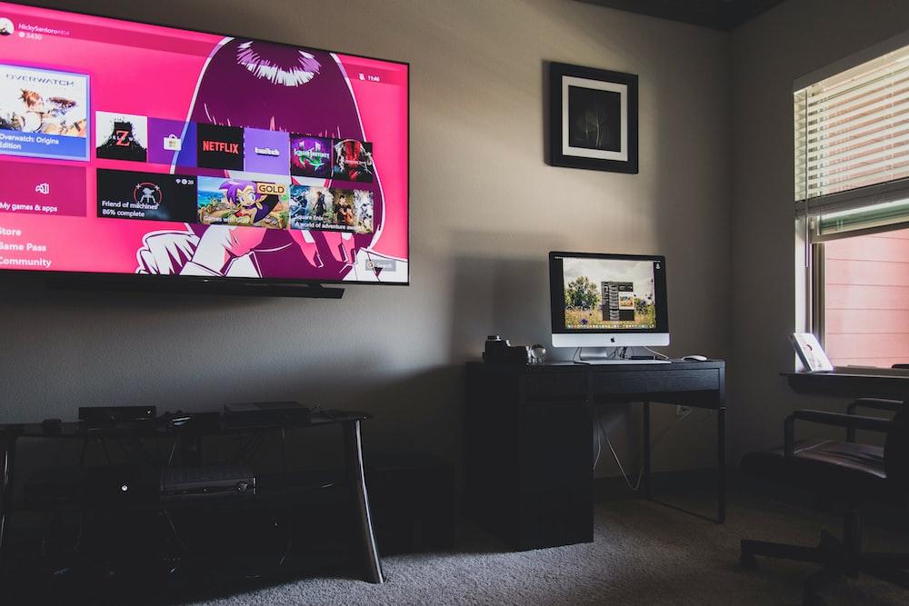 black flat screen tv turned on near black wooden table