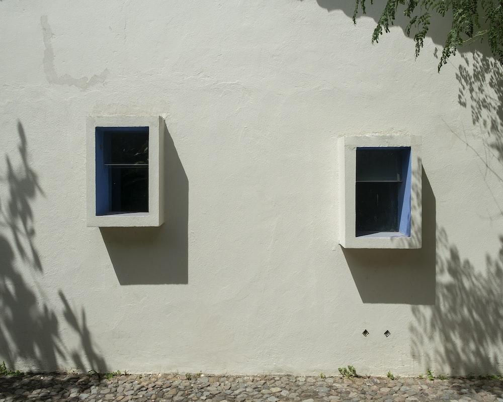 blue wooden window on white concrete wall