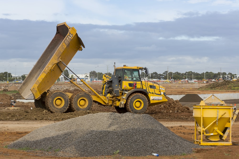 yellow and black heavy equipment on brown dirt field during daytime