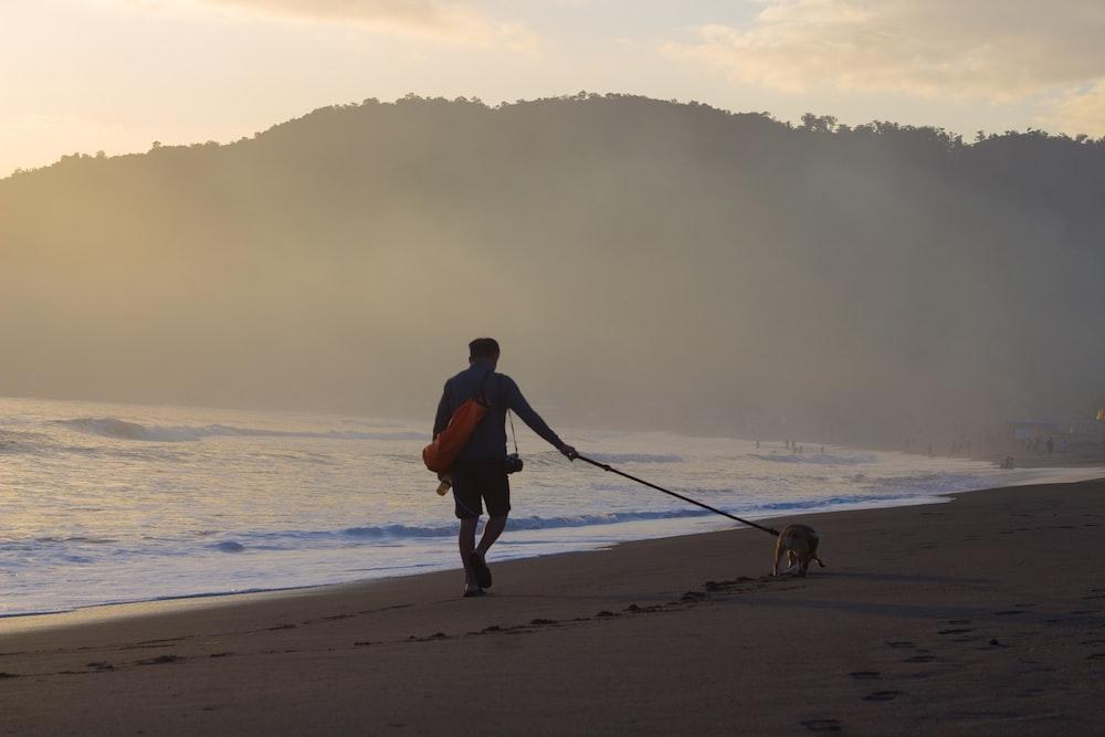 man in orange shirt and black shorts walking on beach during daytime