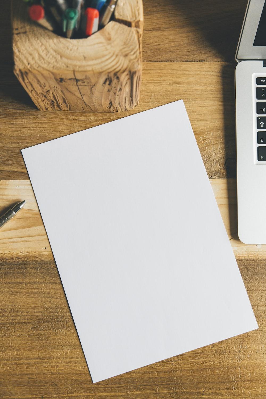 white printer paper beside black pen