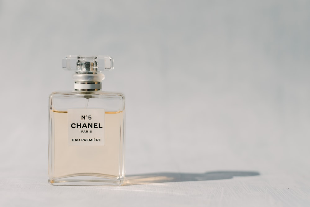 clear glass perfume bottle on white table