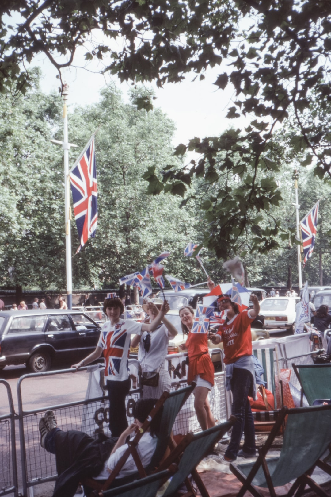 Young people waving British flags waiting for the wedding procession to celebrate the Marriage of Prince Charles and Princess Diana, 1981. 1980s 35mm film slide photo