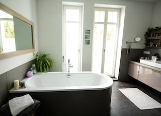 white ceramic bathtub near white wooden framed glass window