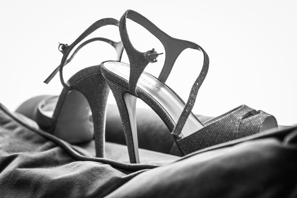 gray scale photo of black leather peep toe heeled sandals