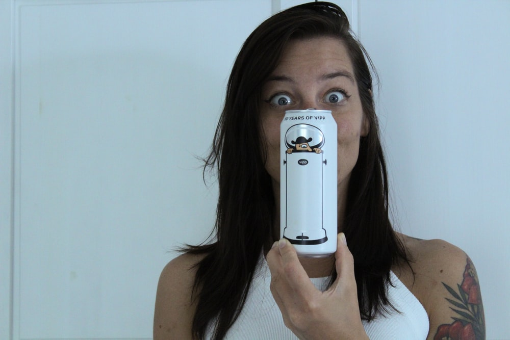 woman in white tank top holding white samsung smartphone