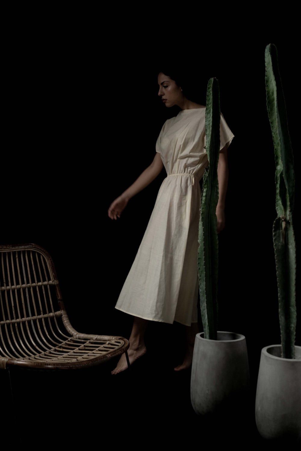 woman in white dress standing beside green curtain