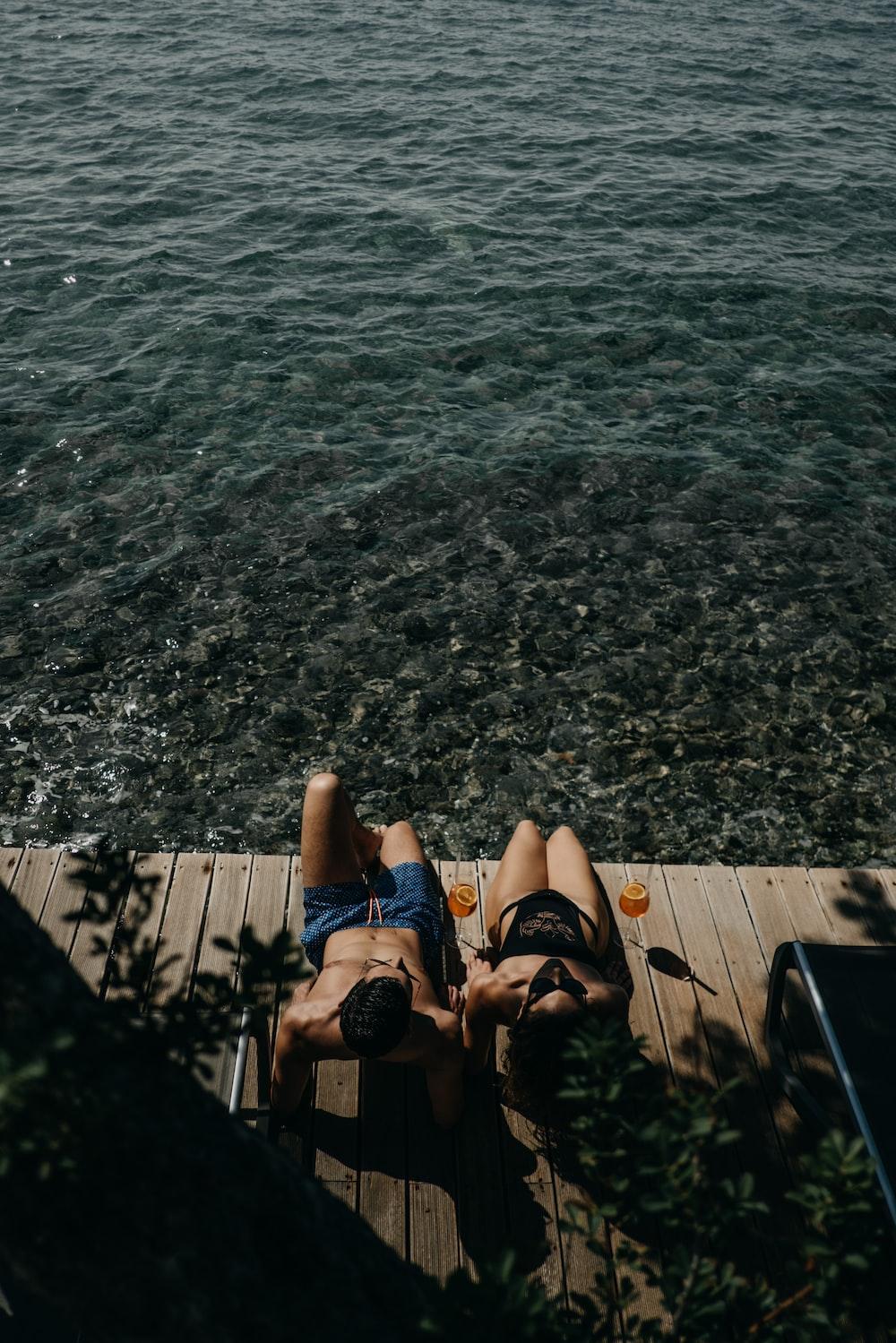 person in black flip flops sitting on wooden dock