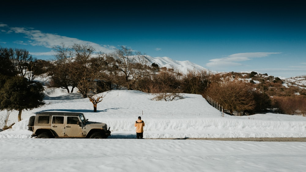 person in yellow jacket standing on snow covered ground during daytime