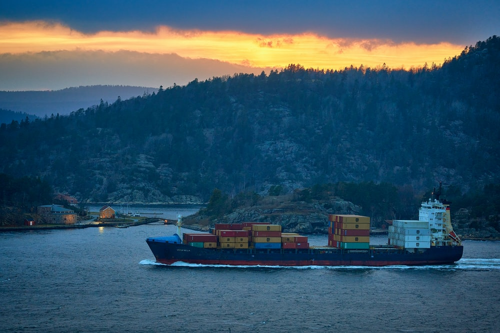 red and white cargo ship on sea during sunset