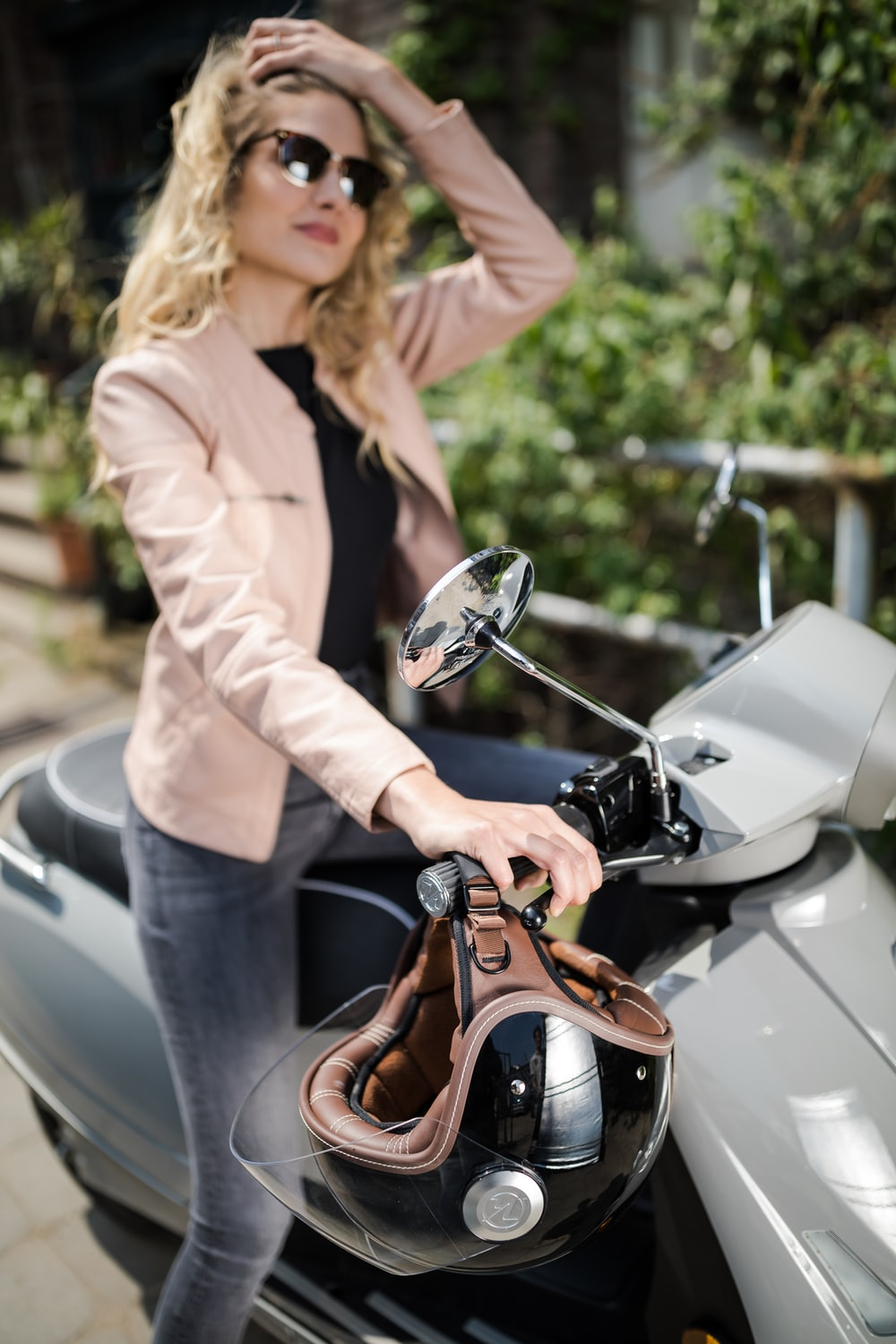 woman in beige coat riding on brown and black motorcycle