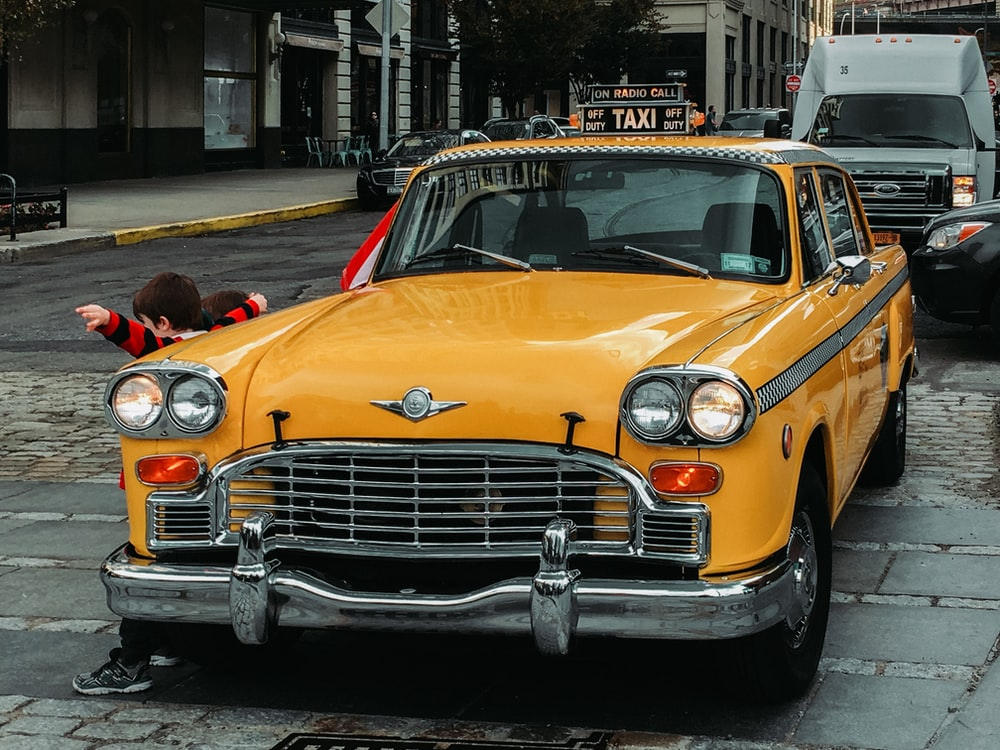 yellow classic car on road during daytime