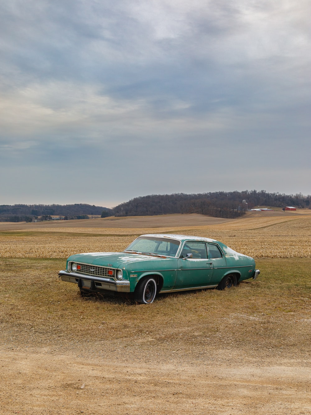 green car on brown field during daytime