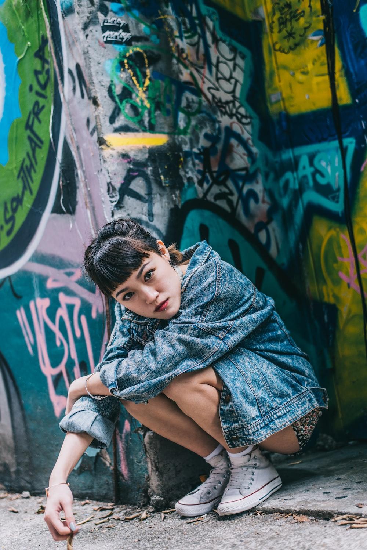 girl in purple dress sitting on concrete wall
