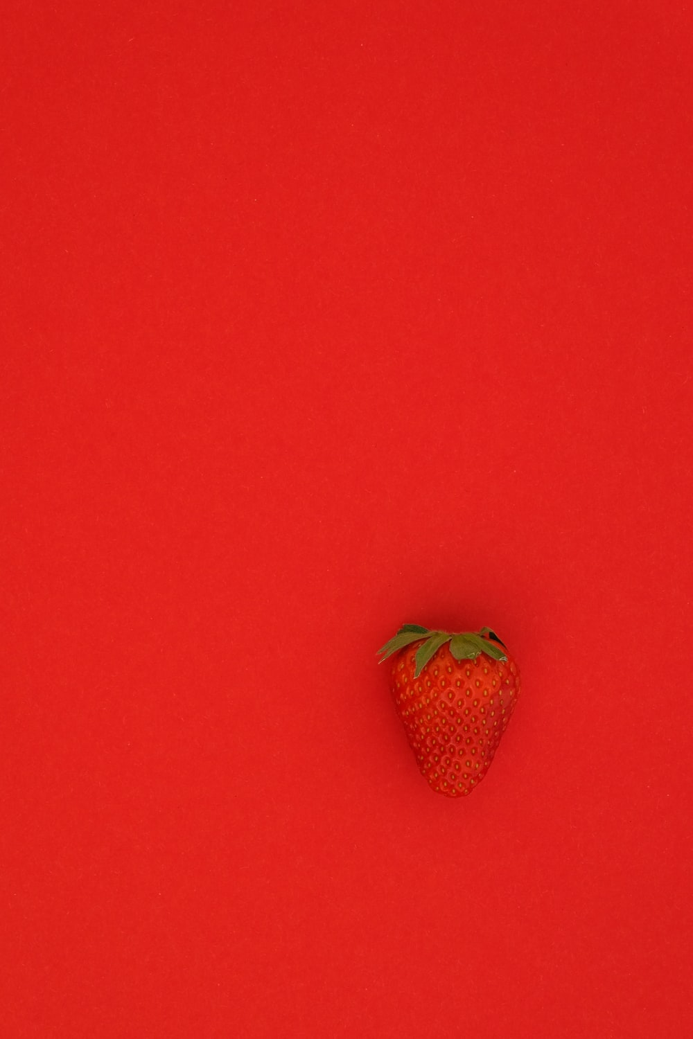 red strawberry fruit on red surface