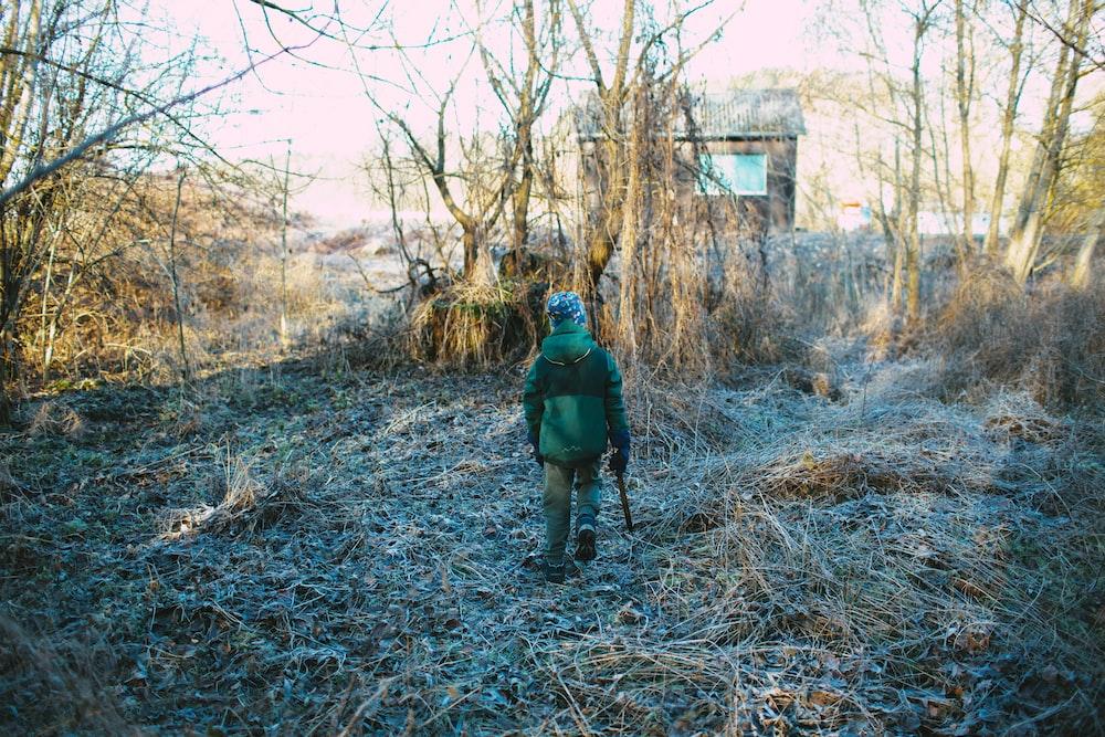 man in green jacket walking on brown dried grass during daytime