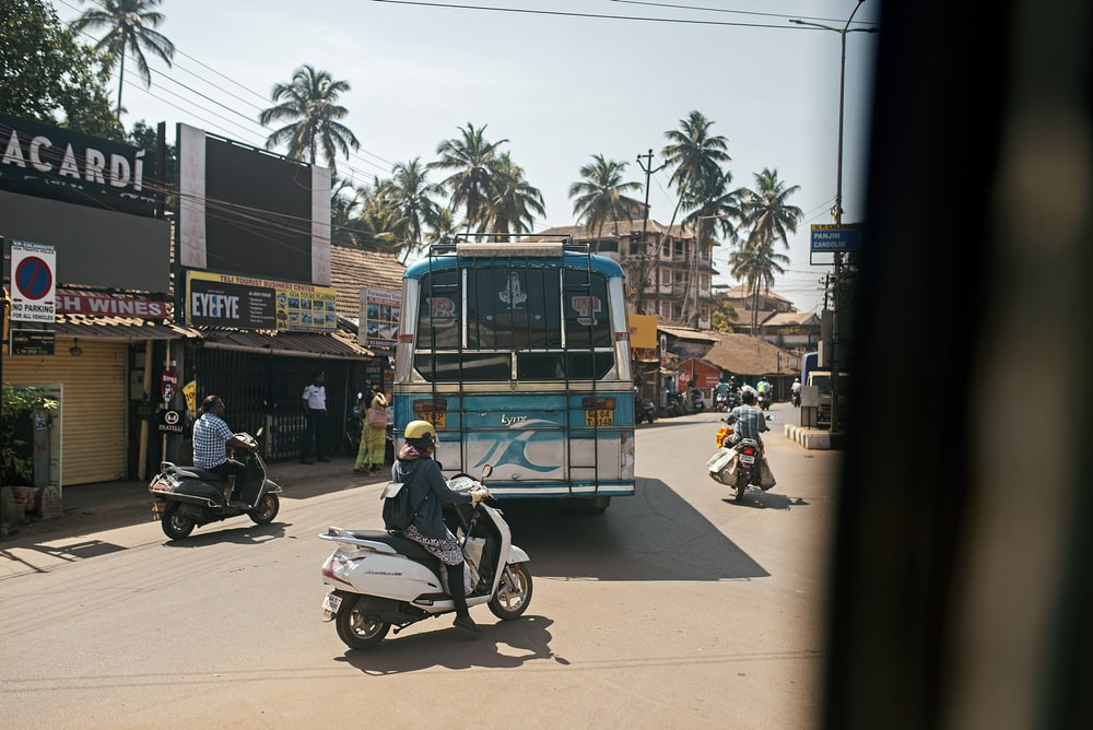 people riding motorcycle near blue bus during daytime