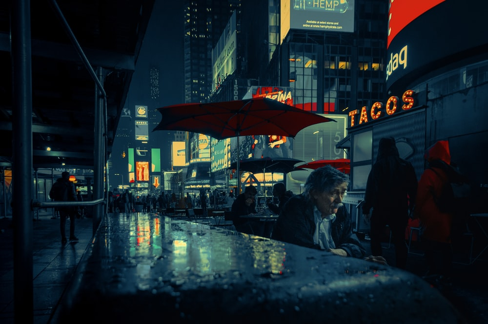 people sitting on chair under red umbrella during night time