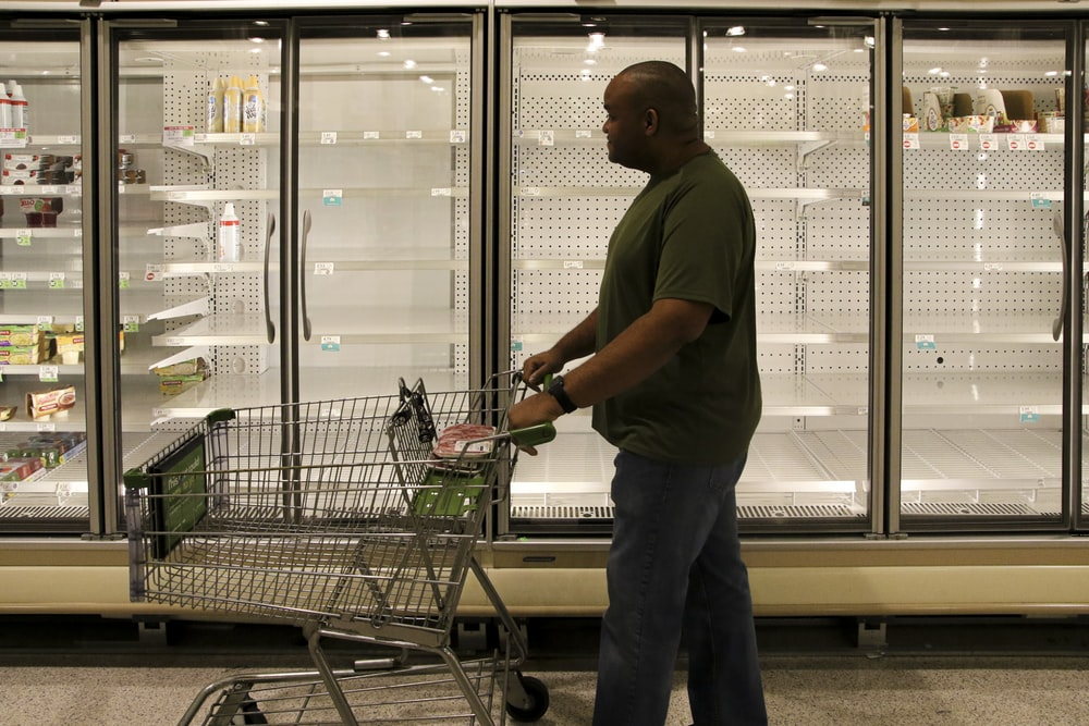 man in brown polo shirt and gray pants standing beside shopping cart