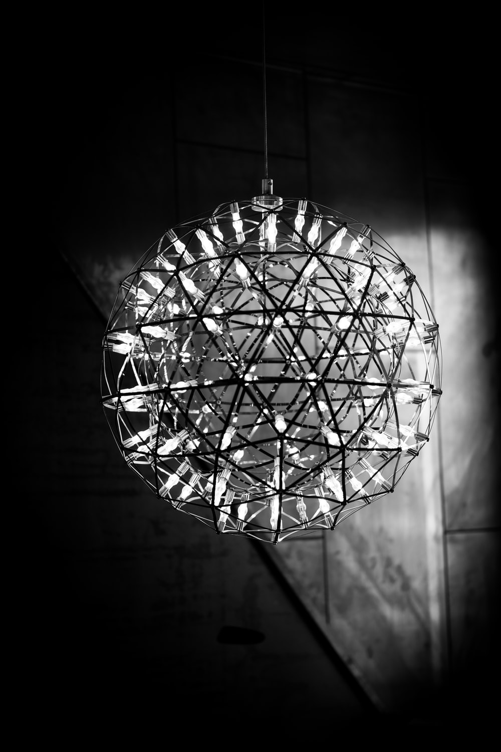 grayscale photo of round glass pendant lamp