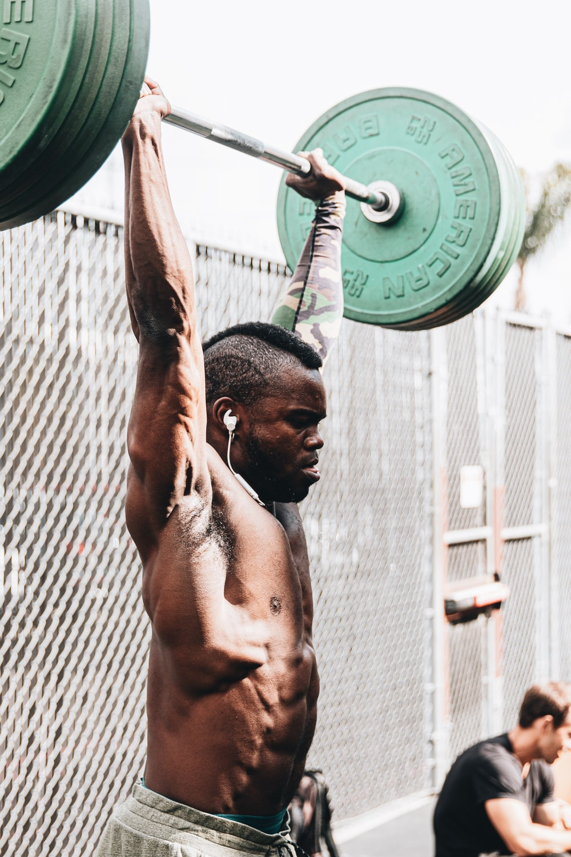 topless man holding green dumbbell