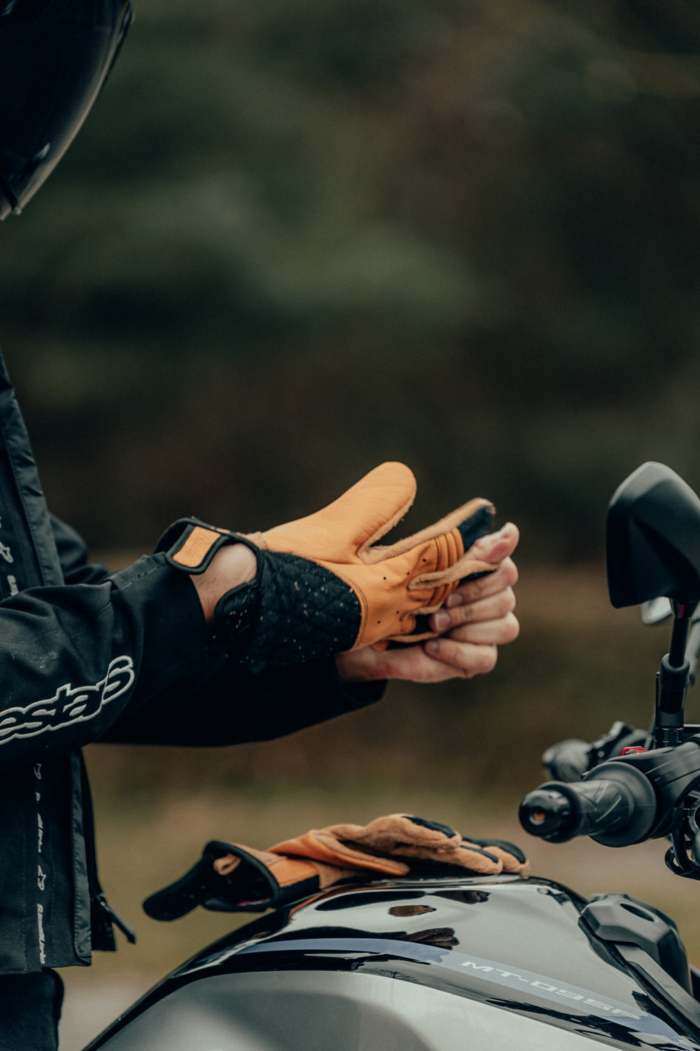 person in black leather jacket holding black and gray bicycle handle bar