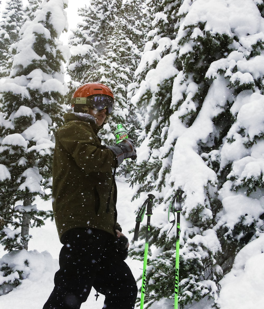 man in brown jacket and red helmet standing on snow covered ground during daytime