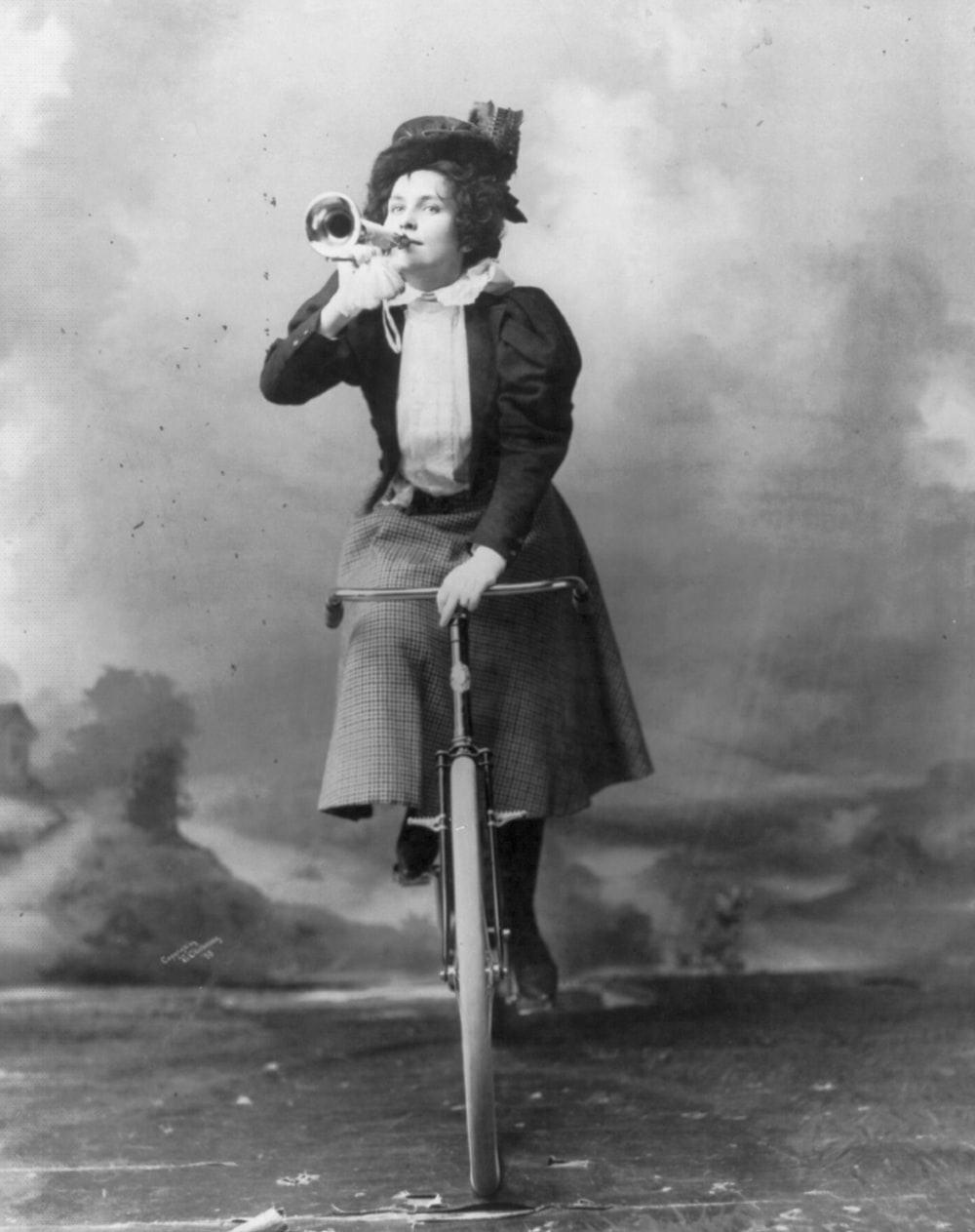 Madge Lessing, full length, on bicycle, holding musical horn to lips