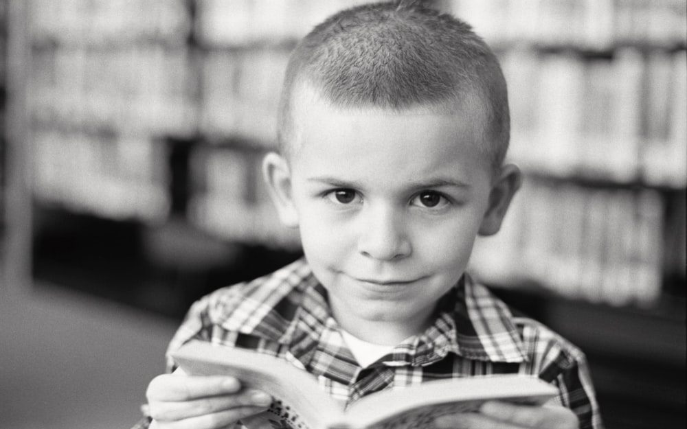grayscale photo of boy in plaid shirt