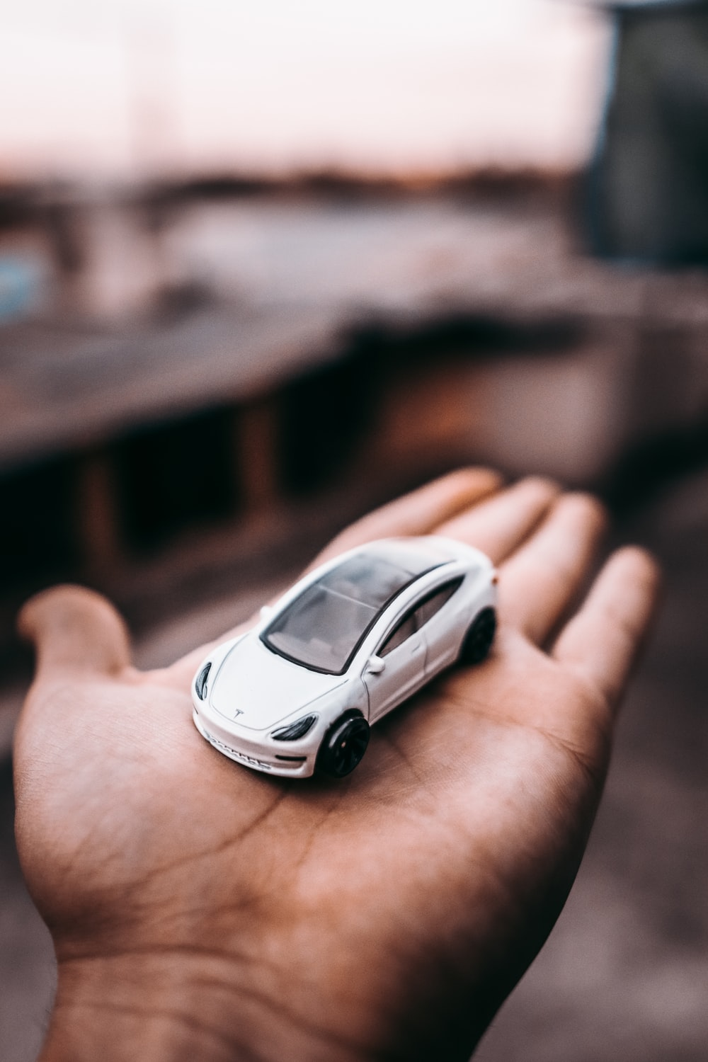 person holding white and black car scale model
