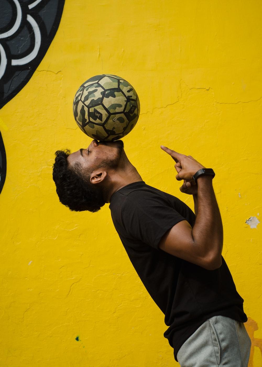 man in black crew neck t-shirt holding black and white soccer ball