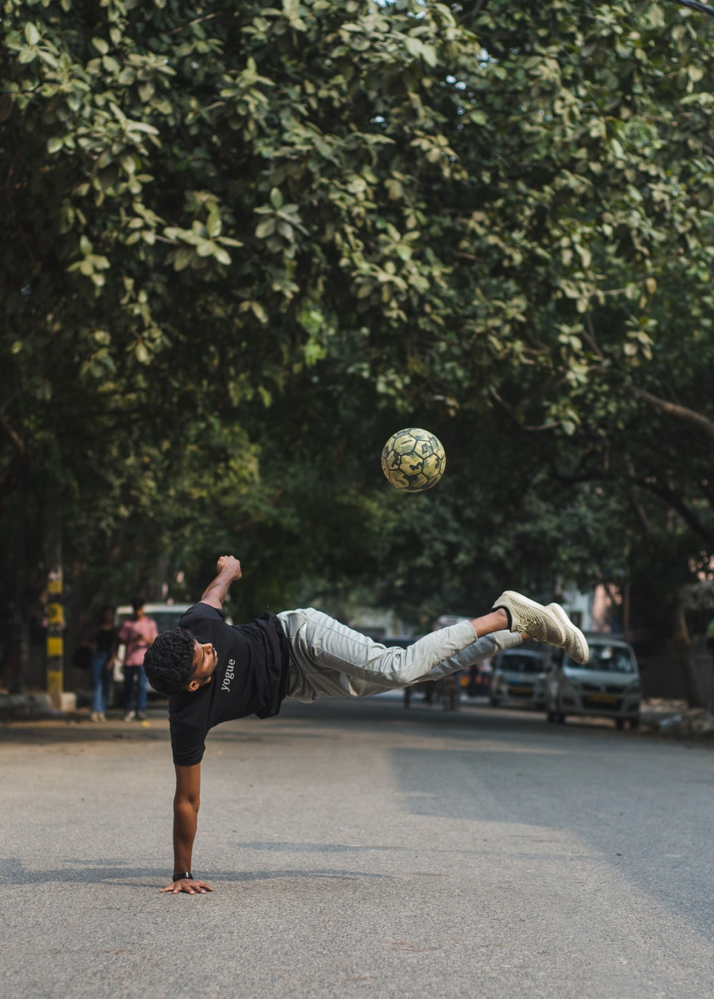 man in black t-shirt and white pants playing soccer during daytime