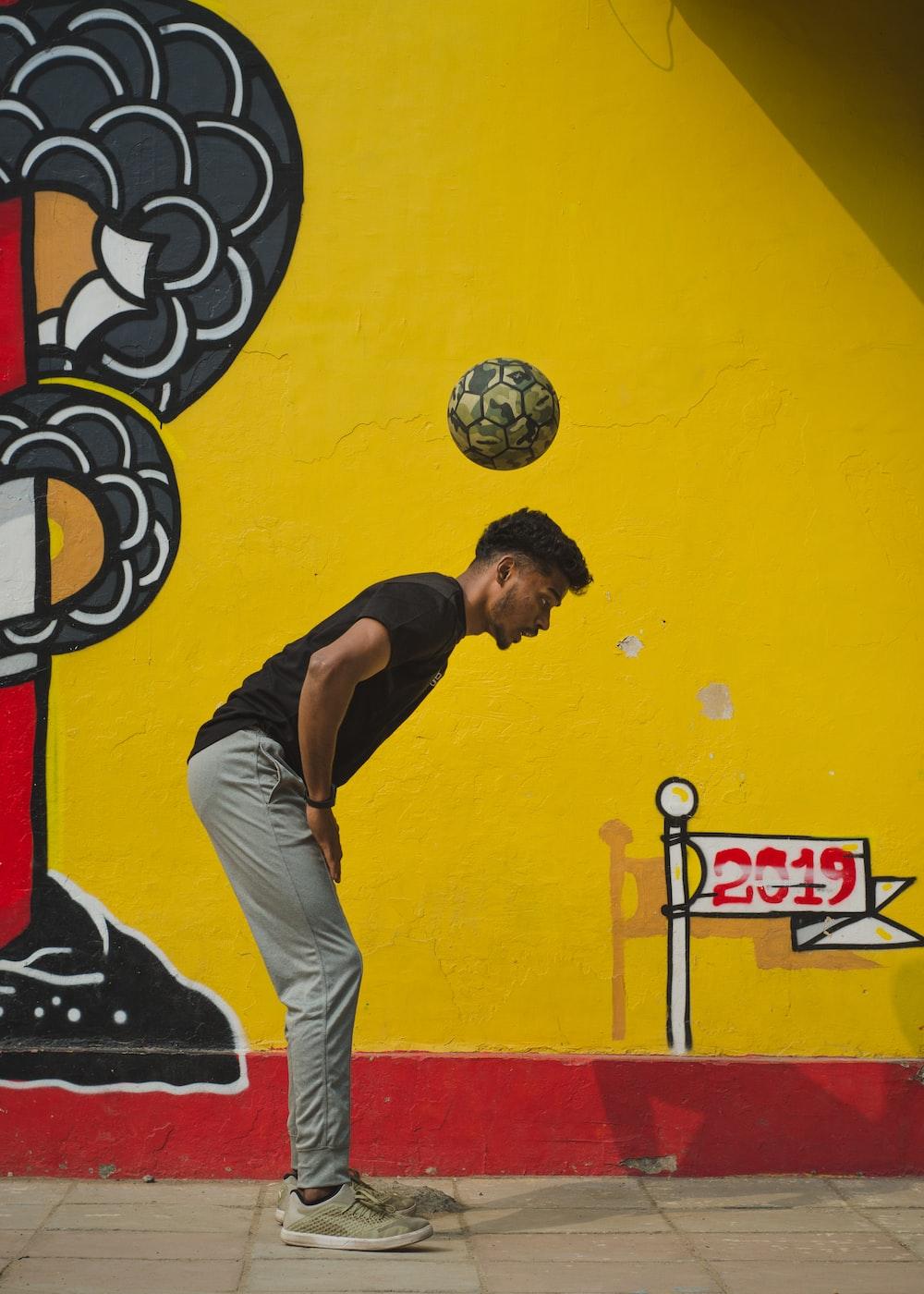 man in black shirt and gray pants playing soccer ball