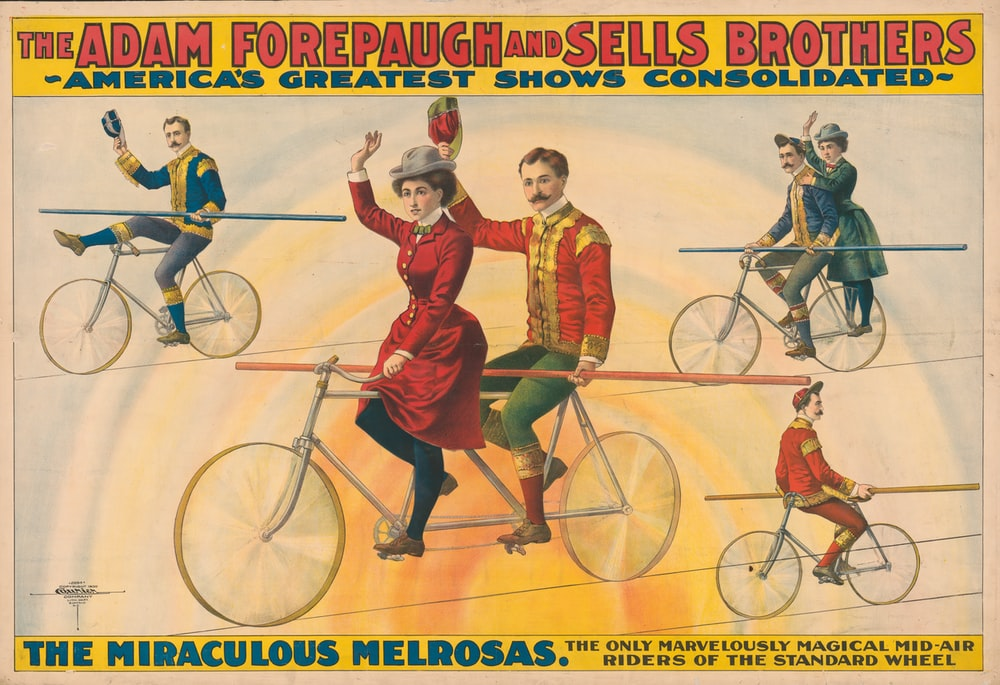 Circus poster showing bicycle riders on tightrope.