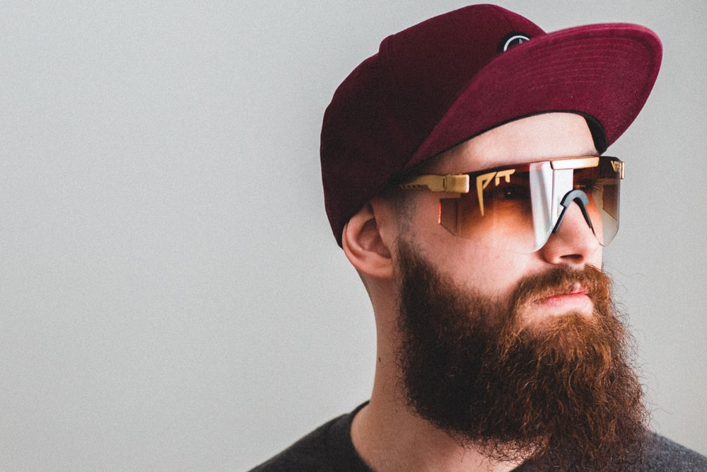 man in black crew neck shirt wearing black sunglasses and red cap