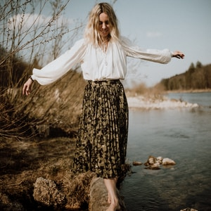 woman in white long sleeve shirt and black and white floral skirt standing on brown rock
