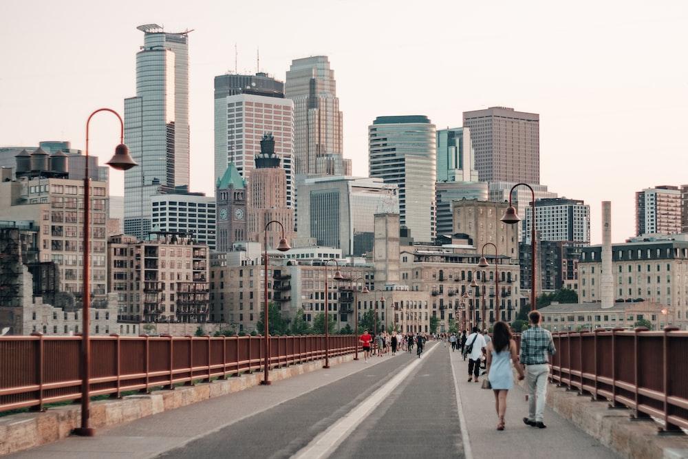 people walking on sidewalk near city buildings during daytime