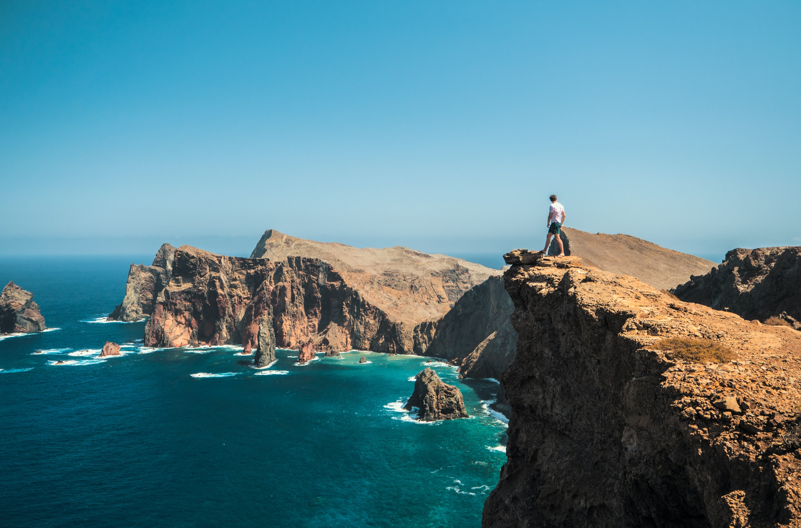 man standing on brown rock formation near blue sea during daytime