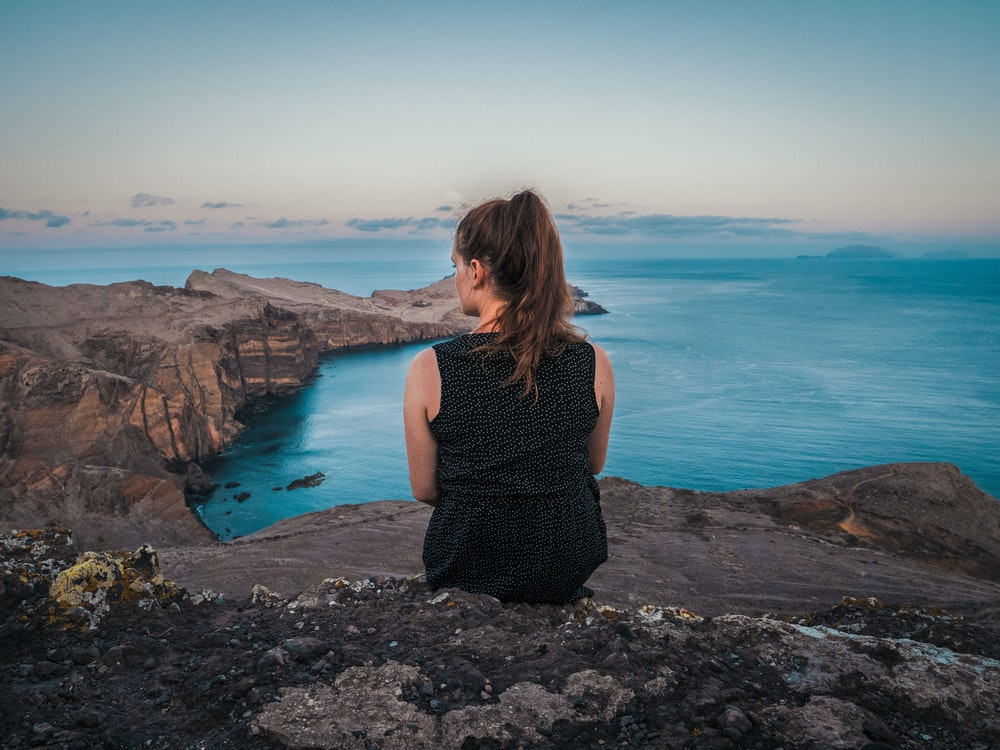 woman in black tank top sitting on rock near body of water during daytime