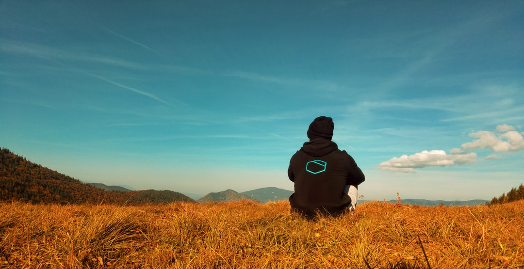 Man in hoodie sitting on golden fields under the clouds near the mountains