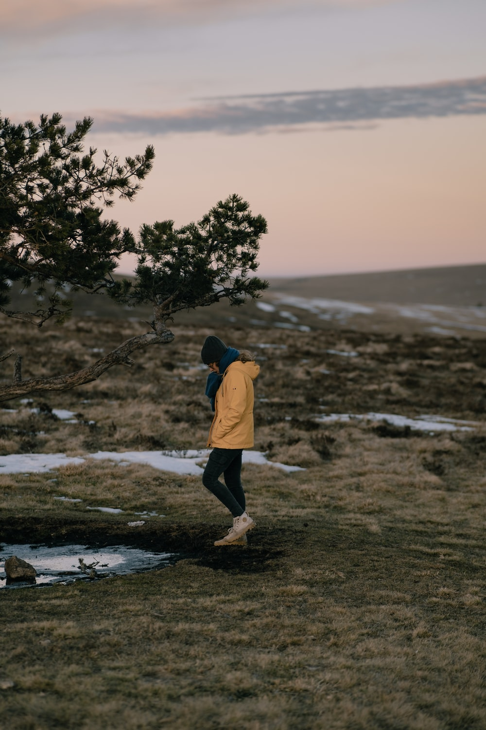 person in yellow hoodie standing on seashore during daytime