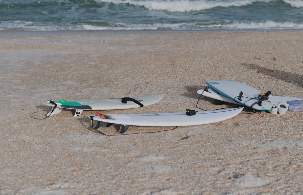 white and blue surfboard on brown sand beach during daytime