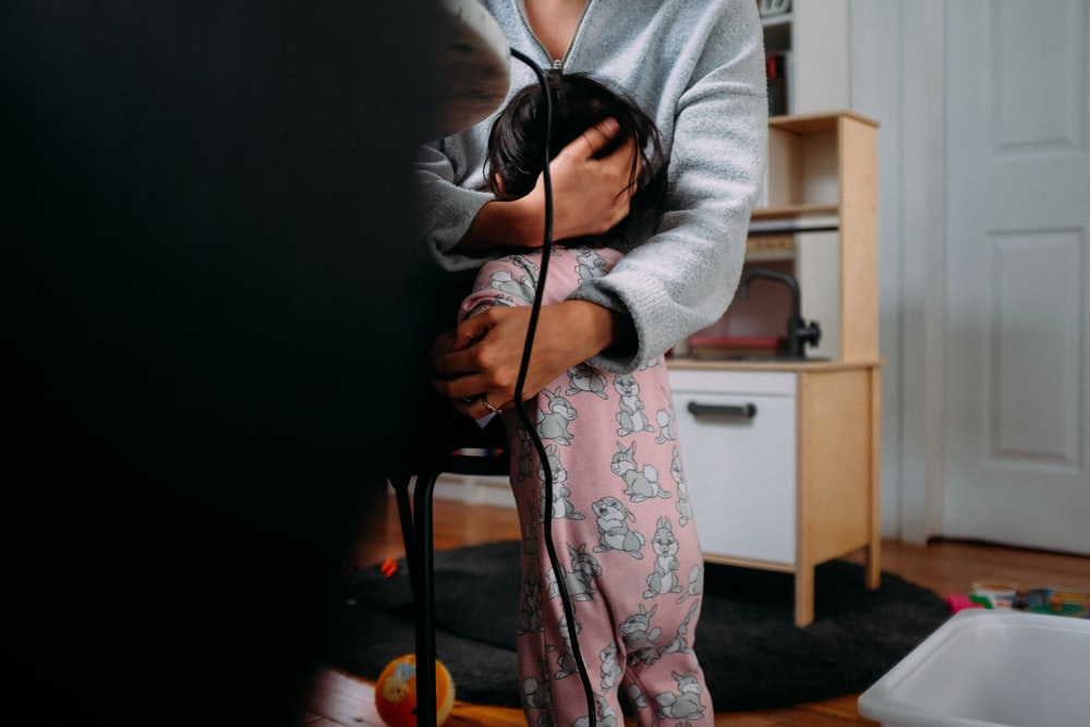 woman in gray cardigan and pink floral dress holding black coated wire
